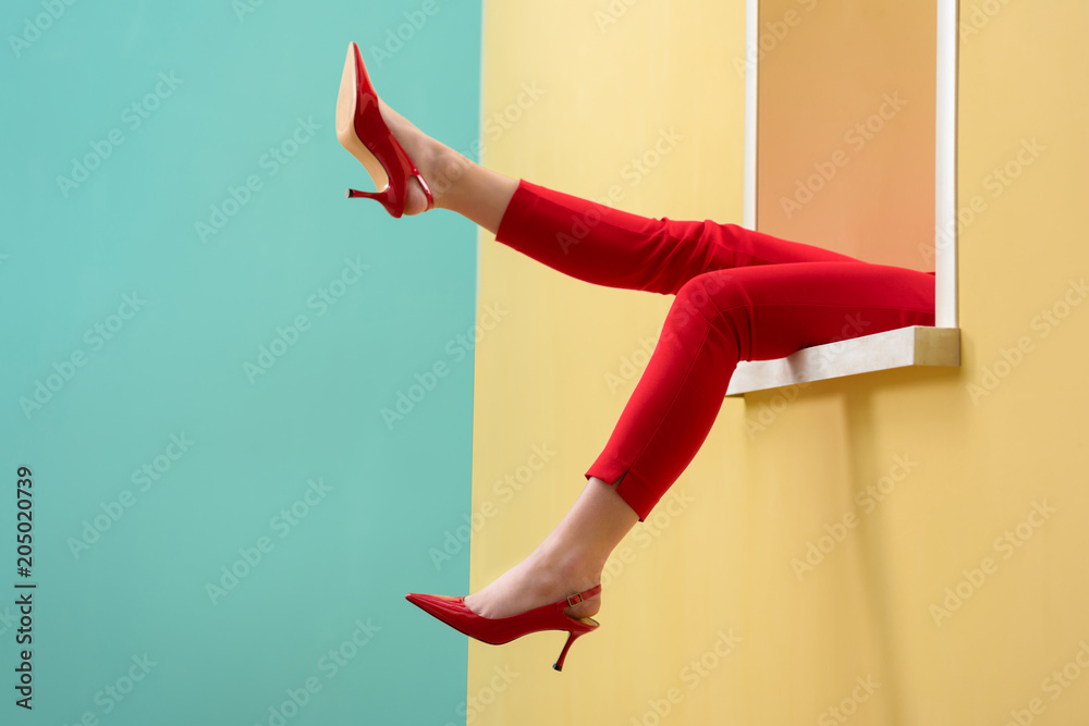 Fototapety, obrazy: partial view of woman in red pants and shoes outstretching legs out decorative window