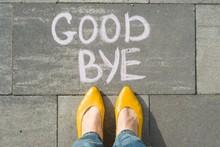 Female Feet With Text Goodbye Written On Asphalt