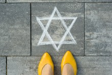 Female Feet With Abstract Image Of A Six-pointed Star, Written On Grey Sidewalk.