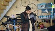 Concentrated repairman is greasing mechanism while repairing bicycle in nice workshop. Young man in warm vest and protective gloves is listening to music .