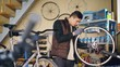 Self-employed mechanic is repairing bicycle wheel with wrenches professional instruments while working in small workshop. Young man is listening to music with earphones.