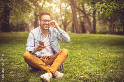 Man listening music at park. - 205044586