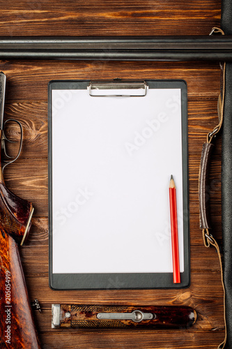 Fotobehang Jacht Blank clipboard and pen with hunting equipment on the wooden background.