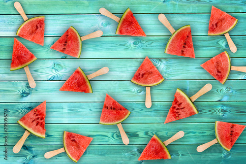 Watermelon slice popsicles on blue wood background, fresh summer fruit concept