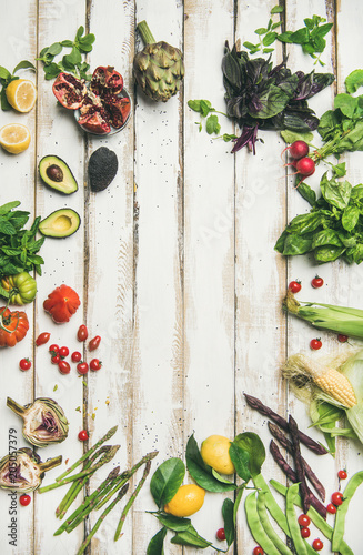Healthy raw summer vegan ingredients. Flat-lay of colorful vegetables and greens on white table background, top view, copy space. Clean eating, dieting party food
