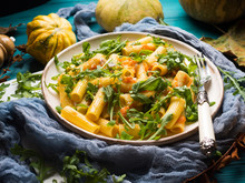 Pasta With Baked Pumpkin, Arugula And Onion. Rustic Green Autumn Background With Pumpkins And Dry Leaves. Fall Food Still Life Flat Lay