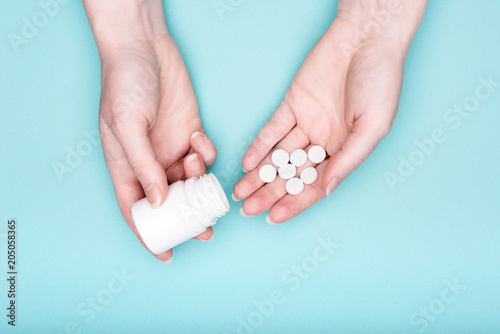 Close up of female hands holding medication bottle and white pills over pastel blue background Wallpaper Mural