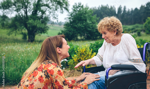 Affectionate young woman talking to elderly woman in a wheelchair in the garden Canvas Print