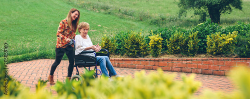 Young woman carrying her mother in a wheelchair through the garden Canvas Print
