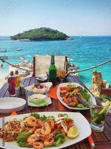 Fresh seafood on the table in summer cafe on the Mediterranean coast. Location famous place Ksamil beach, Saranda popular coastal Albanian resort, Albania, Europa. Beauty world. Mobile photography.