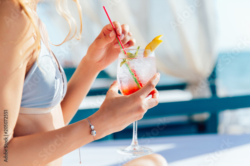Plakát  Female in swimsuit holds a glass of fresh cocktail
