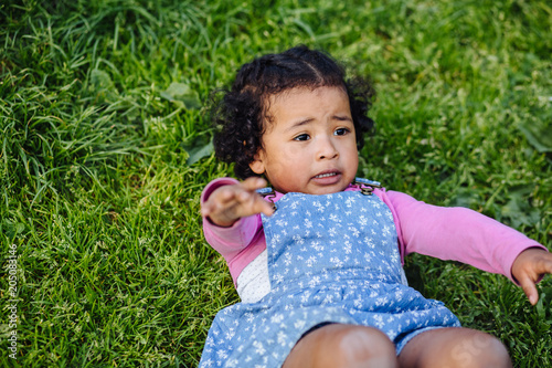 Valokuva  Dark skinned hispanic toddler girl reaching hand for help with hand while lying on the grass in the summer day in park