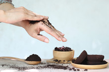 Woman Hand With Scrub Coffee Grounds On Wooden Background, Beauty And Healthy Care Concept