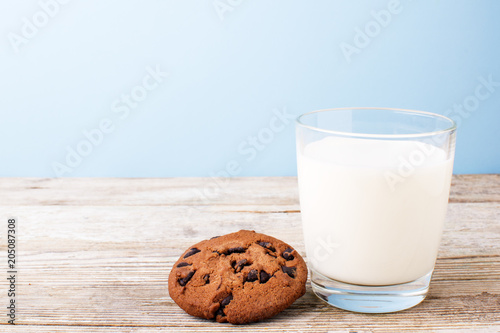 Foto op Canvas Koekjes chocolate chip cookies and a glass of milk on a light table, on a blue background