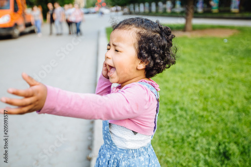 Fotografia, Obraz  Portrait of dark skinned active hysteric hispanic or mexican toddler girl crying and stretching out her hand