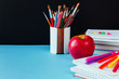 School and office supplies on classroom table in front of blue black blackboard. View with copy space concept back to school