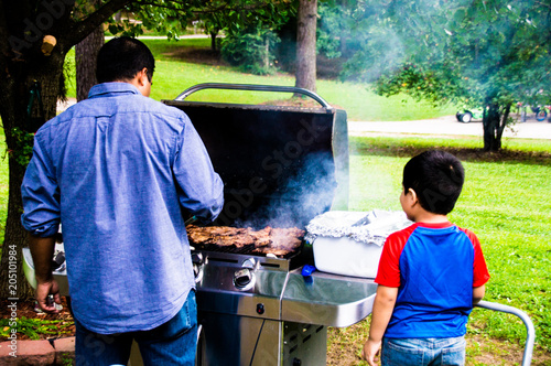 Fotografie, Obraz  Latino dad cooking on a grill outside while son watches