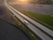 Aerial View Of Highway With Cargo Truck Driving By At Spring Sunset
