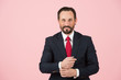 canvas print picture - Smiling bearded manager in blue suit isolated on pink background. Handsome aged businessman in suit is looking at camera and smiling
