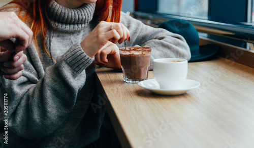 Foto auf Gartenposter Schokolade a girl in a cafe stirs, eating a hot chocolate spoon. the guy opens the sugar for coffee, tea in a white mug that is on the table.