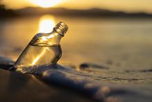 Botella De Ron Llena De Agua Mientras Las Olas La Bañan En Una Playa Filipina Con Un Atardecer De Fondo