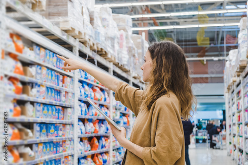 Fotografía  Young business woman with a tablet selects household chemicals in a supermarket