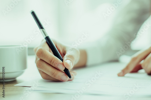 Fototapeta Hand of young businesswoman writing on paper or signing contract at table in office obraz