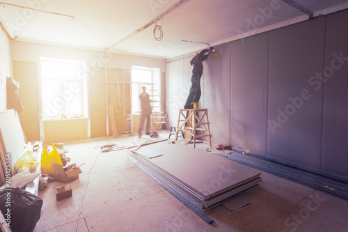 Fotografia, Obraz  Workers are installing plasterboard (drywall) for gypsum walls in apartment is under construction, remodeling, renovation, extension, restoration and reconstruction