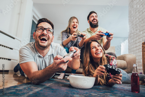 Group of friends play video games together at home, having fun. Fototapet