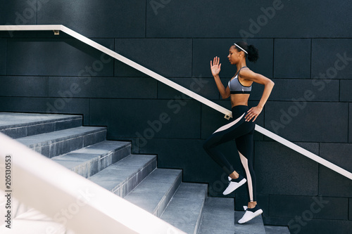 Photo  Side view of woman in sportswear  running up the steps in the city