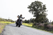 From below shot of anonymous man in helmet driving motorbike on paved remote road in nature.