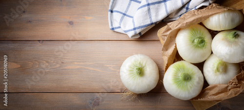 Onion flat white with paper bag on wood background. Top view, space for text