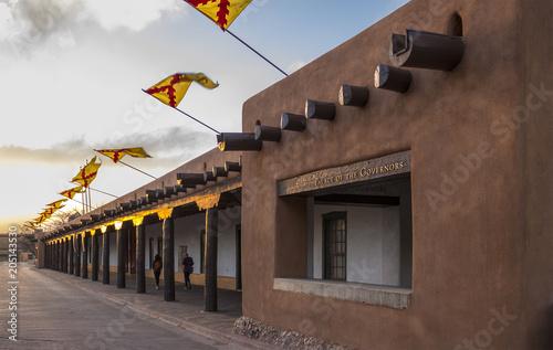 Naklejka premium Flagi latające nad Pałacem Gubernatorów, Santa Fe Plaza, stolicą stanu Nowy Meksyk o zachodzie słońca w wiosenny wieczór. Struktura Adobe i historyczna hiszpańska siedziba rządu na południowym zachodzie.