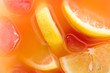 close up view of fresh cocktail with ice cubes and lemon pieces background
