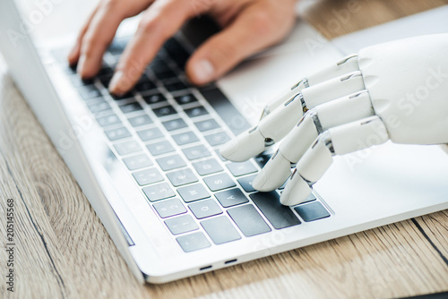 Photo  close-up view of human and robot hands typing on laptop at workplace