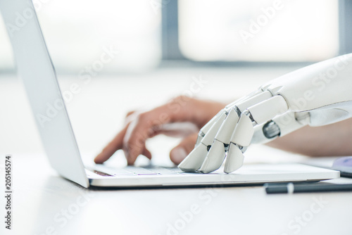 selective focus of human and robot hands typing on laptop at workplace Canvas Print