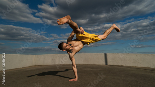 Papiers peints Combat Tricking on street. Martial arts. Man performs blow with support of his hand barefoot. Shooted from bottom foreshortening against sky.
