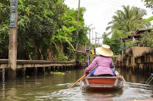 Photo  Woman rowing a boat in floating market, Damnoen Saduak District near Bangkok, Ratchaburi, Thailand