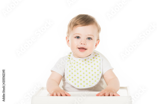 Fotografie, Obraz smiling baby boy in bib sitting in highchair isolated on white background