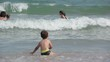 A happy children jumping through the sea waves on a summer vacation