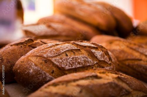Deurstickers Bakkerij Close-up of fresh white bread in rolls stands in even rows in a bakery