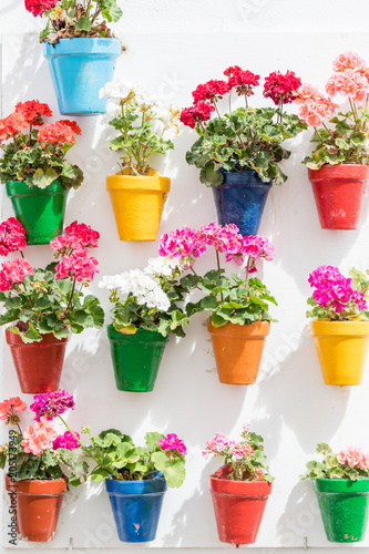 Cordoba, Spain - April 28, 2018: series of vases hanging on the wall with colorful flowers