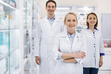 Come Here. Enthusiastic Three Pharmacists Smiling To Camera While Staying In Drugstore