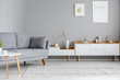 Leinwanddruck Bild - Grey settee near white cupboard in scandi living room interior with posters on the wall. Real photo