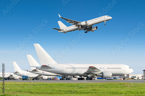 Passenger aircraft row, airplane parked on service before departure at the airport, other plane push back tow Canvas Print