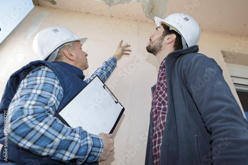 Fototapeta builder inspecting roof damage obraz