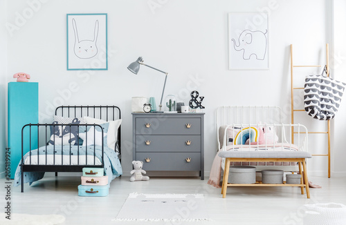 Poster Jacht Grey cabinet with lamp between black and white bed in siblings bedroom interior with posters. Real photo