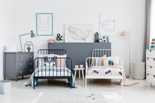 Black And White Bed In Colorful Kids Bedroom Interior With Posters And Lamp On Cabinet. Real Photo