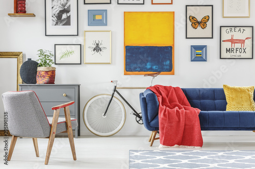 Red blanket thrown on blue settee in bright sitting room interior with patterned armchair, bike and many posters hanging on the wall