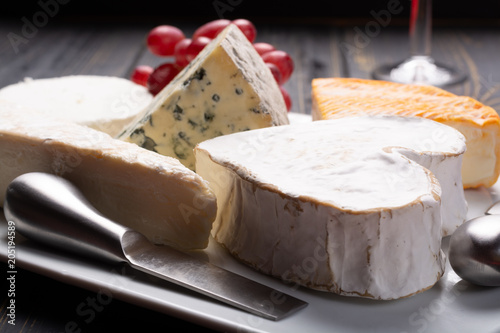 Foto op Aluminium Assortiment French cheeses plate in assortment, blue cheese, brie, munster, soft goat cheese, Neufchatel heart shaped cheese